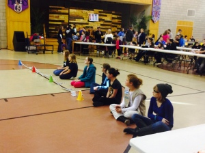 Katarina sits with other Cadettes as their cars race down the track.